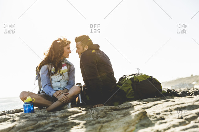 Couple gazing into each other's eyes while sitting by the ocean