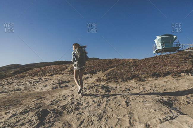Female backpacker walking up a sandy hill
