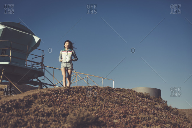 Young woman standing at the top of a hill overlooking the ocean