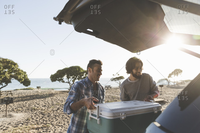 Two men lifting a cooler into the back of a vehicle