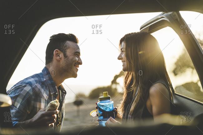 Couple standing by an open car door flirting