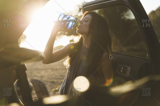 Young woman standing by an open car door drinking water