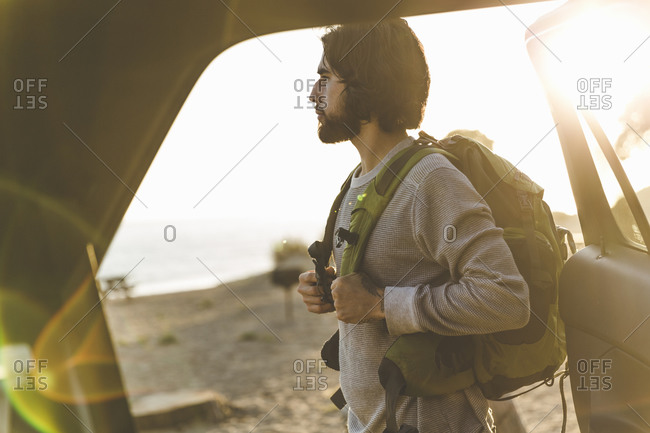 Young man standing by an open car door putting on a backpack