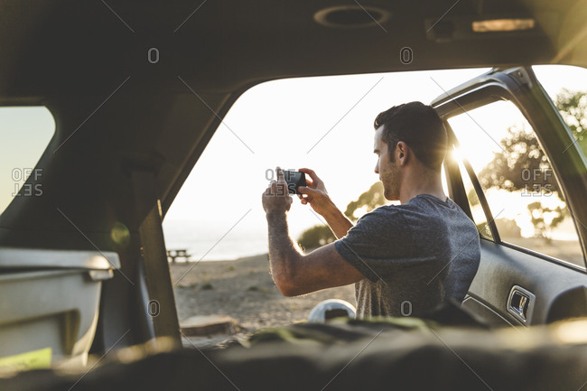 Young man standing by an open car door taking a picture
