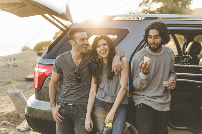 Group of young adults leaning on a vehicle smiling