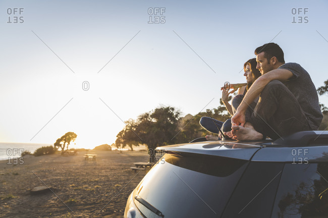 Couple sitting on top of an suv looking at the ocean