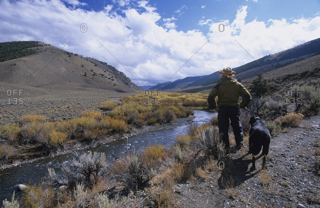 Man and dog hiking above river