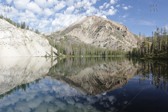 Cliff and mountains reflected in lake