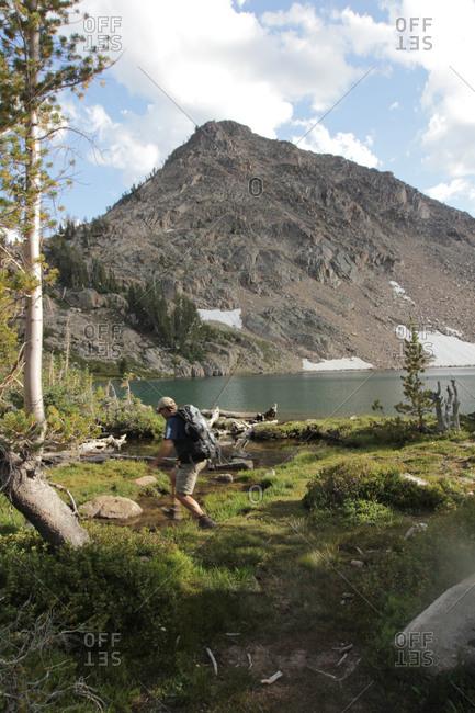 Fisherman hiking on the shore of a lake below mountain