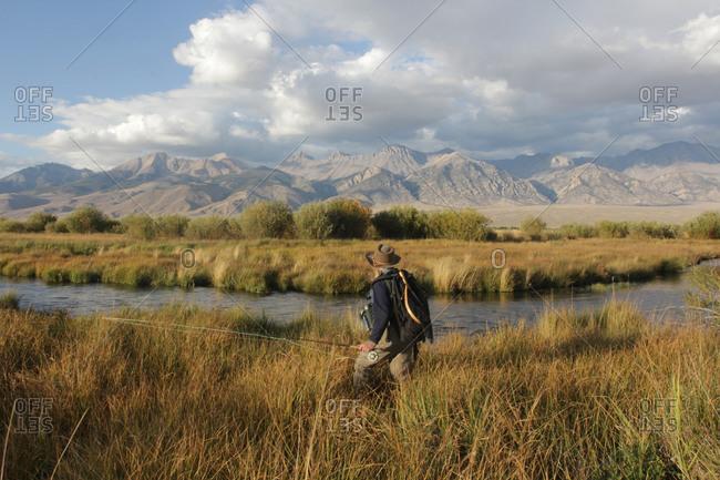 Fisherman walking on banks of stream below mountains