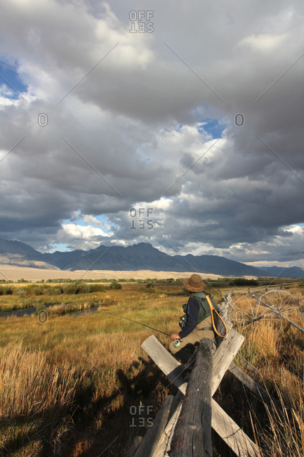 Fisherman sitting on a wooden fence in marshy landscape