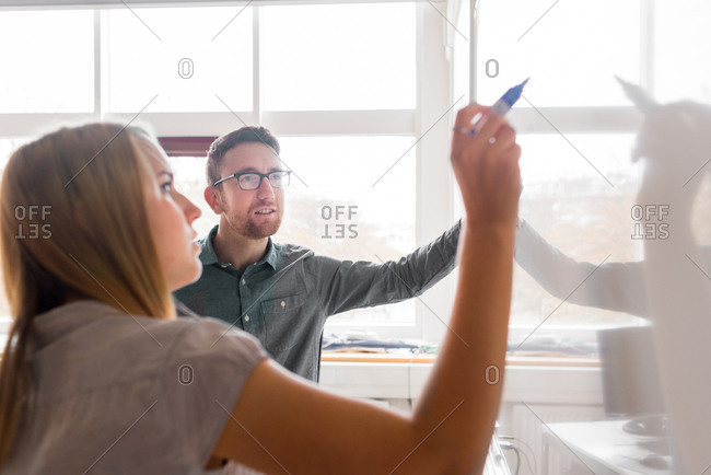 Man and woman working at whiteboard in office