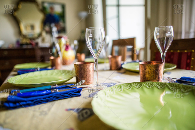 Table set with dishes, wine glass and copper cup for a meal