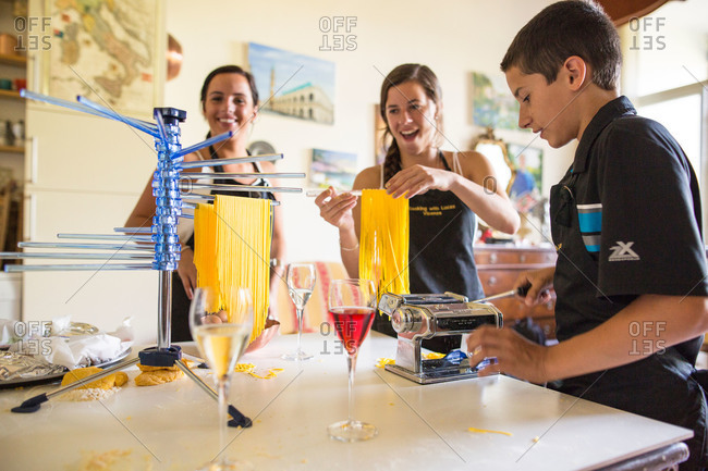 Riva del Garda, Italy - July 11, 2015: Young woman hanging fresh cut noodles on drying rack during a cooking class