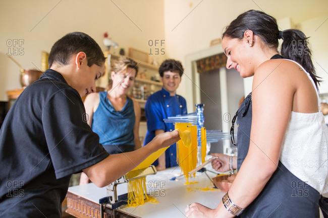 Riva del Garda, Italy - July 11, 2015: Teen boy feeding fresh dough into a pasta cutting machine