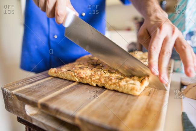 Chef's hands cutting handmade foccacia bread