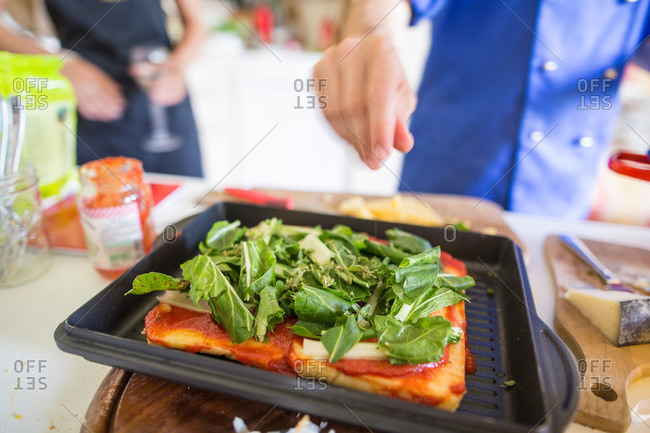Person making pizza with fresh greens