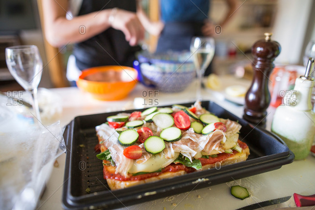 Pizza topped with salad greens, tomatoes and cured pork