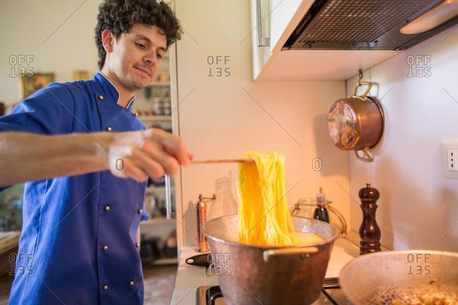Riva del Garda, Italy - July 11, 2015: Chef cooking handmade fresh pasta in kitchen
