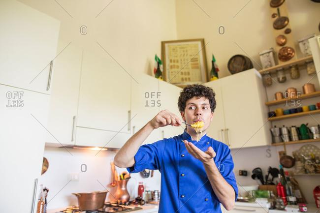 Riva del Garda, Italy - July 11, 2015: Chef glances sideways as he tastes his fresh pasta
