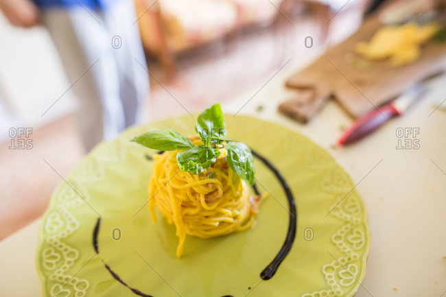 Stack of homemade pasta garnished with basil on plate