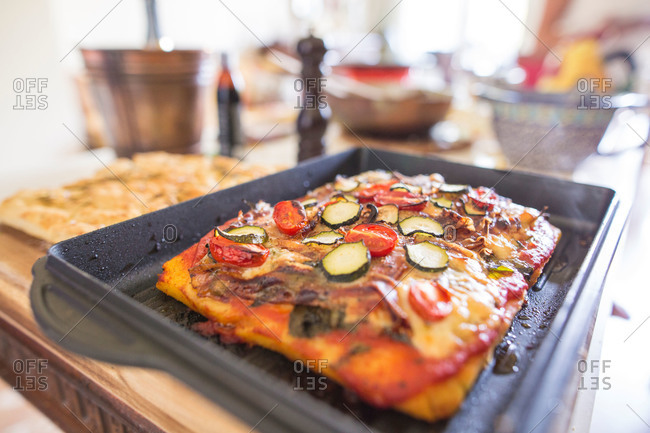Fresh pizza with tomatoes and vegetables in pan