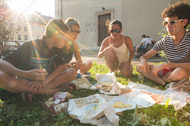 Riva del Garda, Italy - July 11, 2015: People enjoying a picnic lunch on grass in city park, Italy