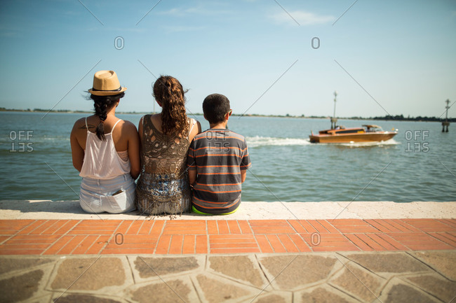 Three children sit together at waterfront in Italy