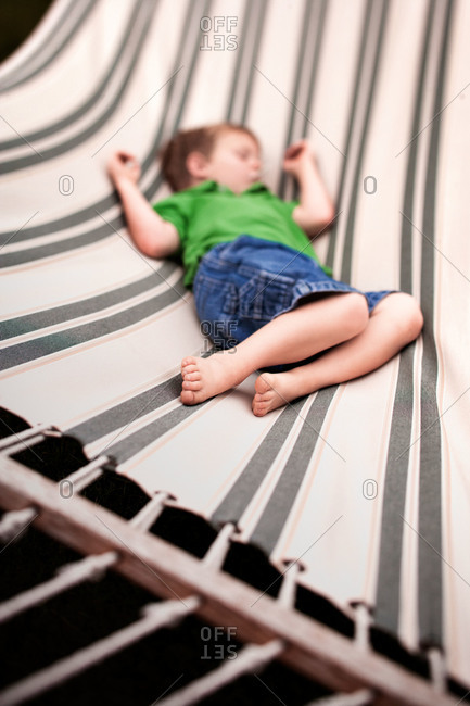 Little boy napping on a hammock