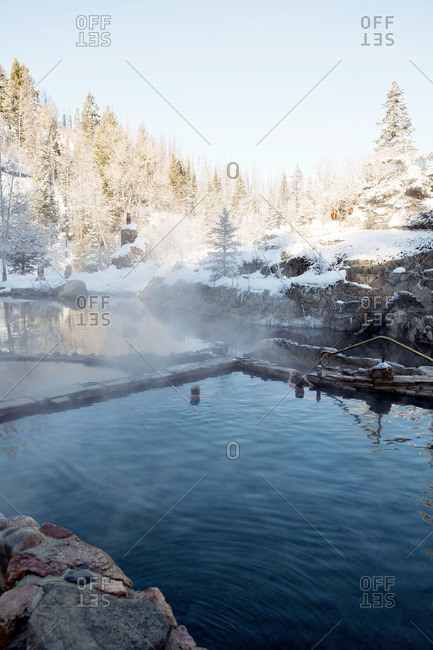 Steam rising from a thermal pool in snowy landscape