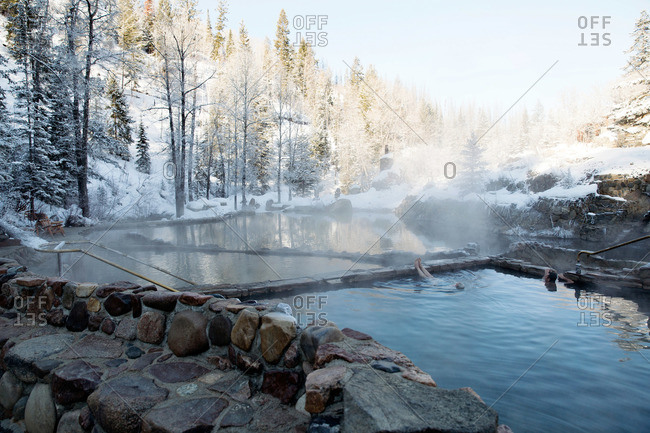 People soaking in a hot thermal pool outdoors in winter