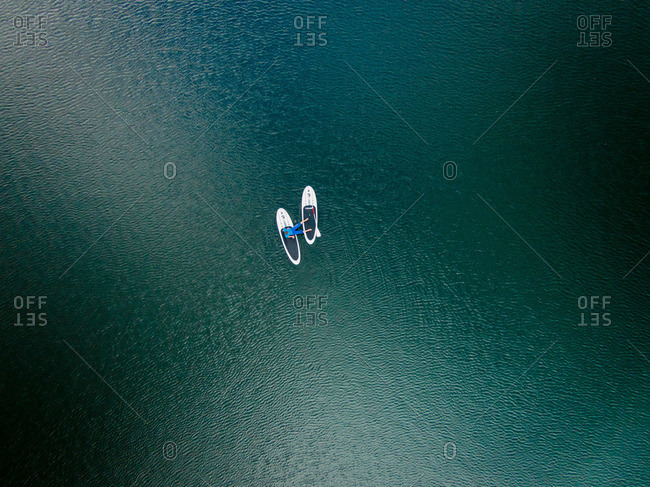 A man sitting on two paddleboards in the middle of a lake