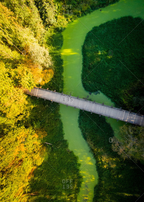 Autumn colors in Lithuania with an aerial view of wooden bridge over a green river