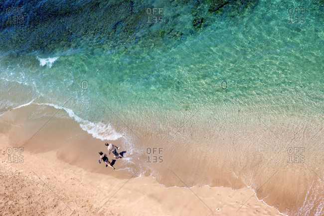 Aerial view of couple strolling on beach