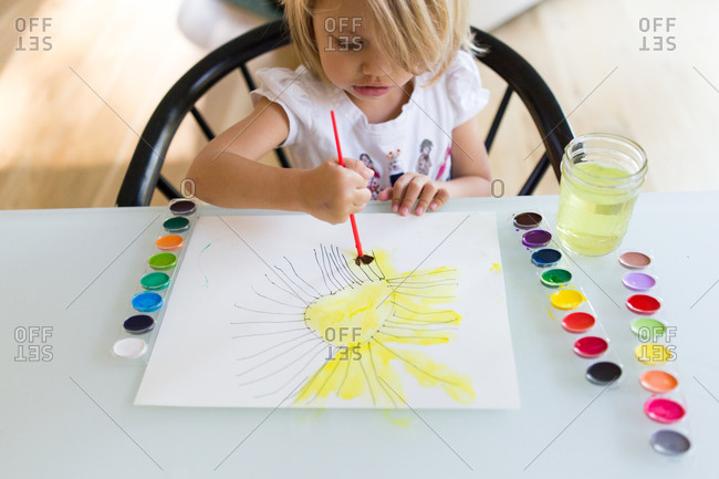 Preschool girl painting with watercolors at table