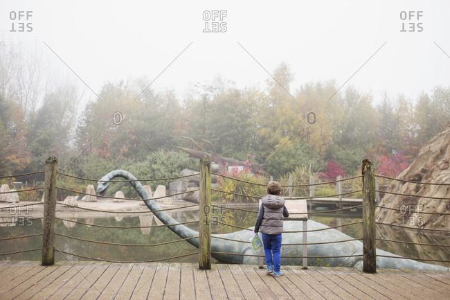 Blackpool, UK - November 1, 2015: Little boy looking at a dinosaur statue at a park