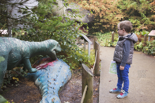 Blackpool, UK - November 1, 2015: Little boy looking at sculptures at a dinosaur-themed park