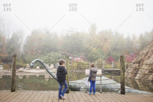 Blackpool, UK - November 1, 2015: Brothers looking at a dinosaur statue at a park