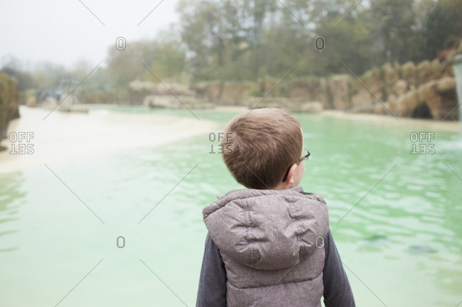 Blackpool, UK - November 1, 2015: Little boy standing in front of a large water feature at a park