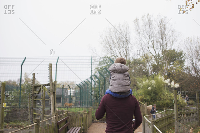 Blackpool, UK - November 1, 2015: Boy sitting on his father's shoulders at a zoo