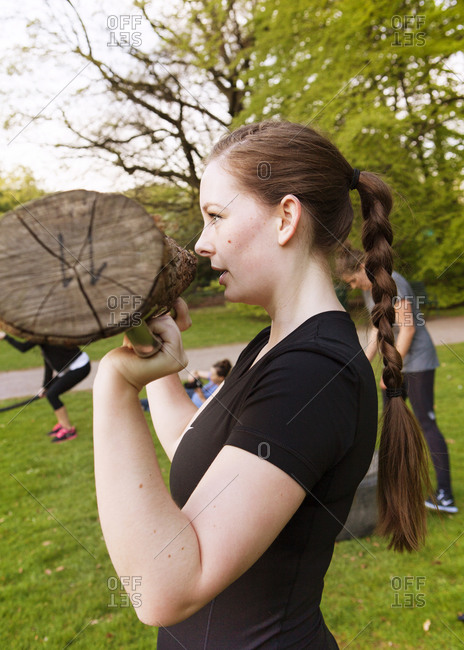 Close up of a young athletic woman weight lifting with a log