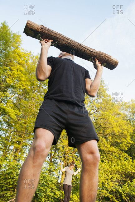 Close up of a young athletic man weight lifting with a log