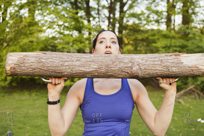 Close up of a young athletic woman lifting a log