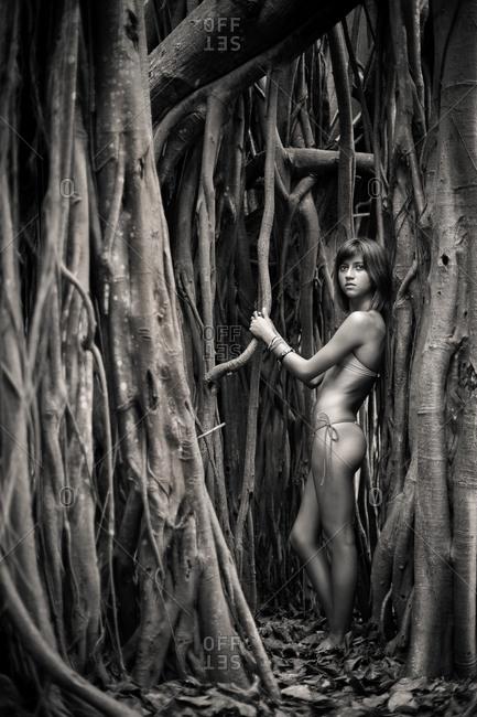 Teenaged girl standing among roots of tree