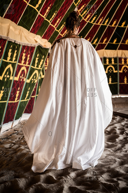 Back view of woman in a white robe inside a tent on sand