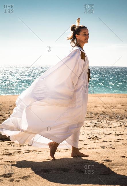 Woman in white robe walking on beach