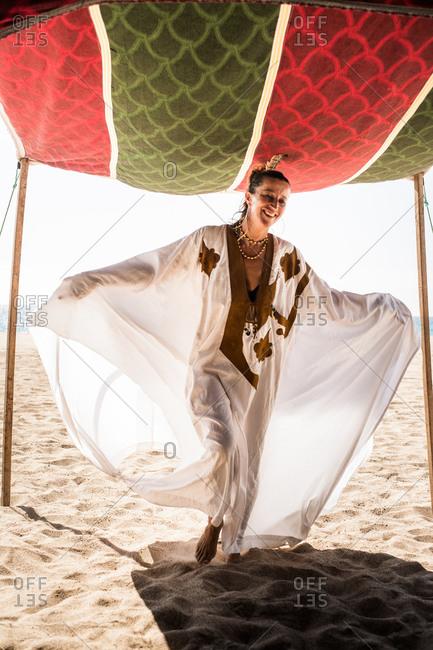 Happy woman in kaftan entering a tent on beach
