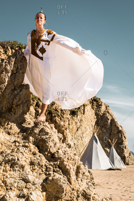 Woman in white dress climbing on rocks on beach with teepee tents