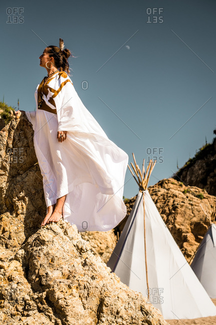 Woman in white dress with feather in her hair standing on rocks near teepee tents