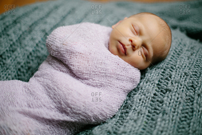 Portrait of a sleeping newborn baby swaddled in a pink blanket